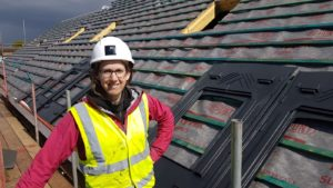 Female engineer on an unfinished roof being fitted with solar panels.